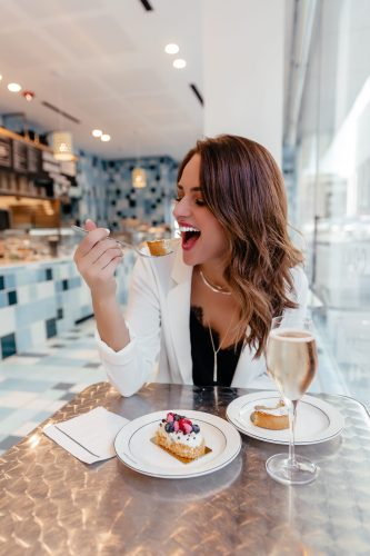 Dallas blogger A Lo Profile eating dessert in a bakery