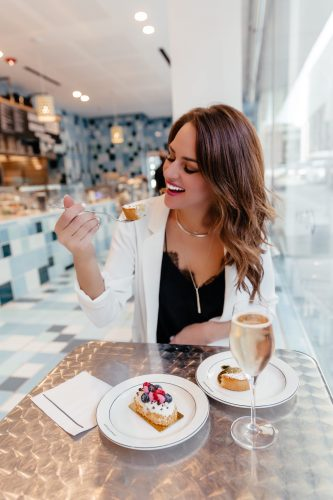 Dallas blogger Lauren Roscopf eating dessert in a bakery