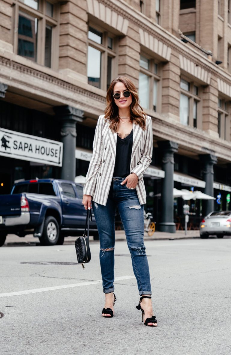 A Lo Profile wearing a white and tan striped Topshop blazer from Nordstrom paired with Hudson distressed skinny jeans, a black cami, Kendra Scott jewelry, a black Topshop bag, Tony Bianco black ruffle heels, round Ray Ban sunglasses, and Kendra Scott jewelry.