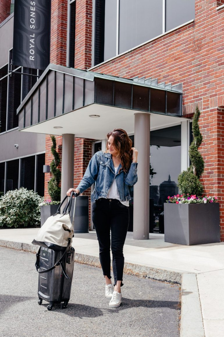 A Lo Profile wearing black skinny jeans with a raw hem, a white t-shirt, and a Paige denim moto jacket with white espadrille sneakers for a casual travel style look.