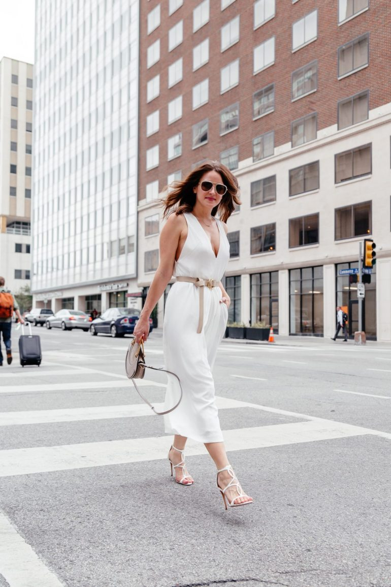 A Lo Profile wearing a white CMEO jumpsuit from Nordstrom with a tan free people belt, gray Chloe bag, and white Schutz shoes
