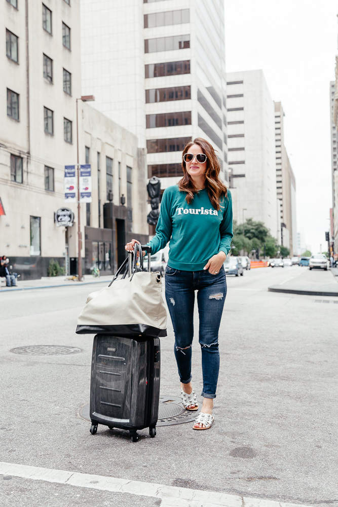 Dallas blogger A Lo Profile wearing a green Wildfox tourista sweatshirt, hudson distressed jeans, white studded marc fisher sandals, and a sole society weekender bag.