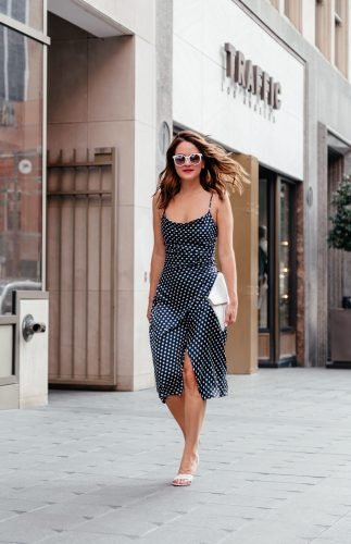 Lauren Roscopf from A Lo Profile wearing a summer slip dress in a navy polka dot print paired with white accessories for a perfect summer look.