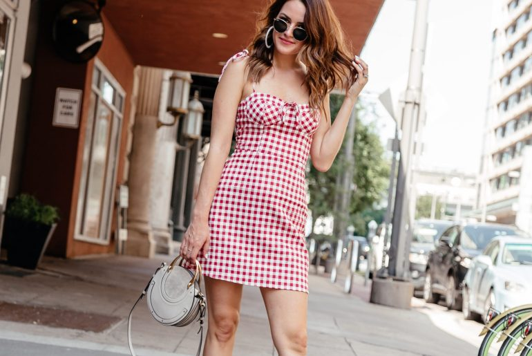 A Lo Profile wearing a red gingham dress by WAYF with white espadrille sneakers, a gray round Chloe Pixie bag, round ray ban sunglasses, and white acrylic hoop earrings from Bauble Bar.