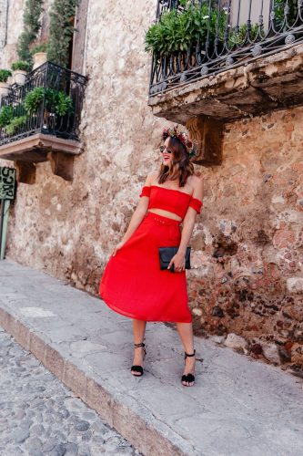 Lauren Roscopf of A Lo Profile wearing a red two piece set by House of Harlow with black lace up Tony Bianco sandals, a Gigi New York clutch with tassel, and black and gold Dior sunnies with turquoise bauble bar hoop earrings in San Miguel de Allende.