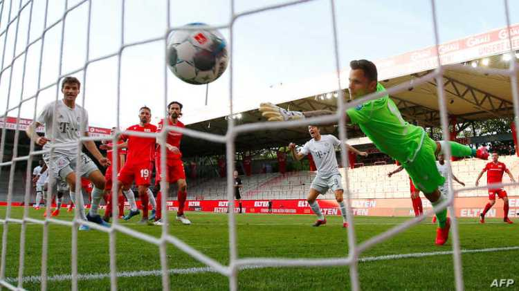 Bayern Munich's French defender Benjamin Pavard (hidden) scores their second goal during the German first division Bundesliga football match FC Union Berlin v FC Bayern Munich on May 17, 2020 in Berlin, Germany as the season resumed following a two-month absence due to the novel coronavirus COVID-19 pandemic. (Photo by HANNIBAL HANSCHKE / POOL / AFP) / DFL REGULATIONS PROHIBIT ANY USE OF PHOTOGRAPHS AS IMAGE SEQUENCES AND/OR QUASI-VIDEO