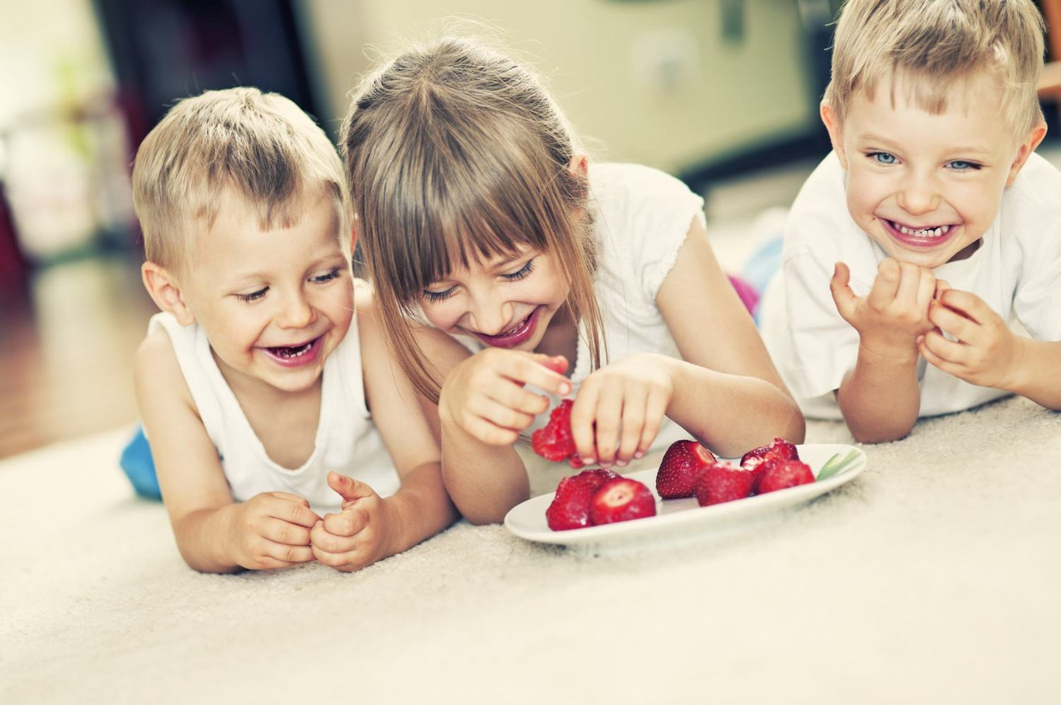 Kids eating strawberries on carpet