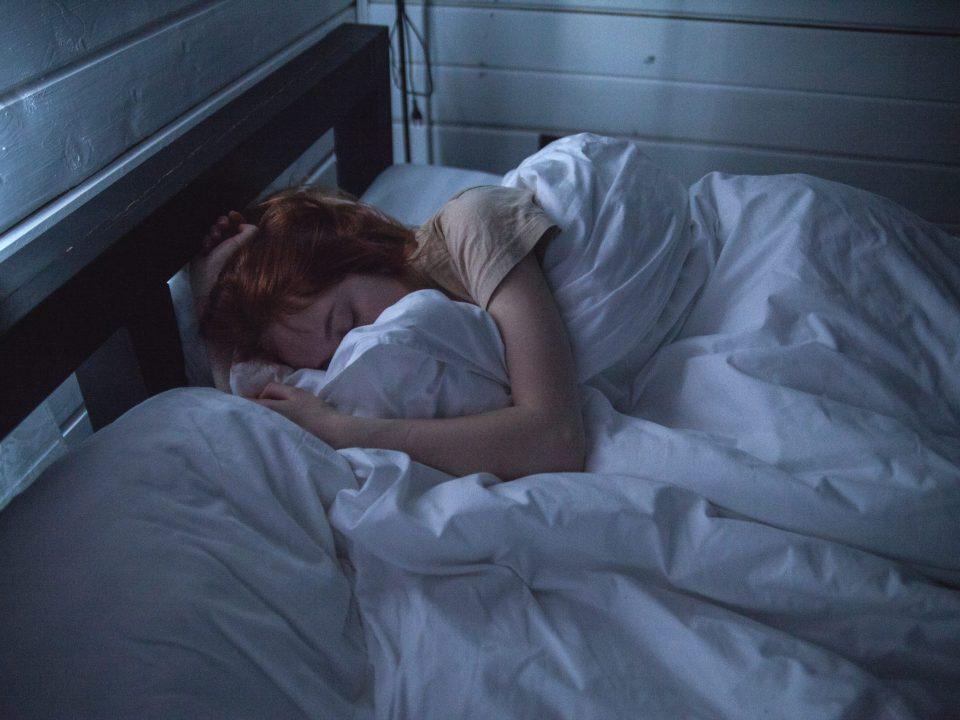 femme rousse endormie lit couette blanche