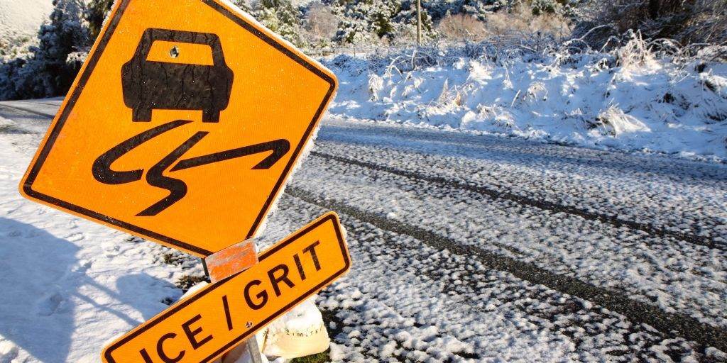 snow covered road with warning sign