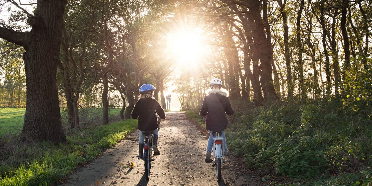 Two young girls wearing helmets bike through a grove of trees towards the setting sun