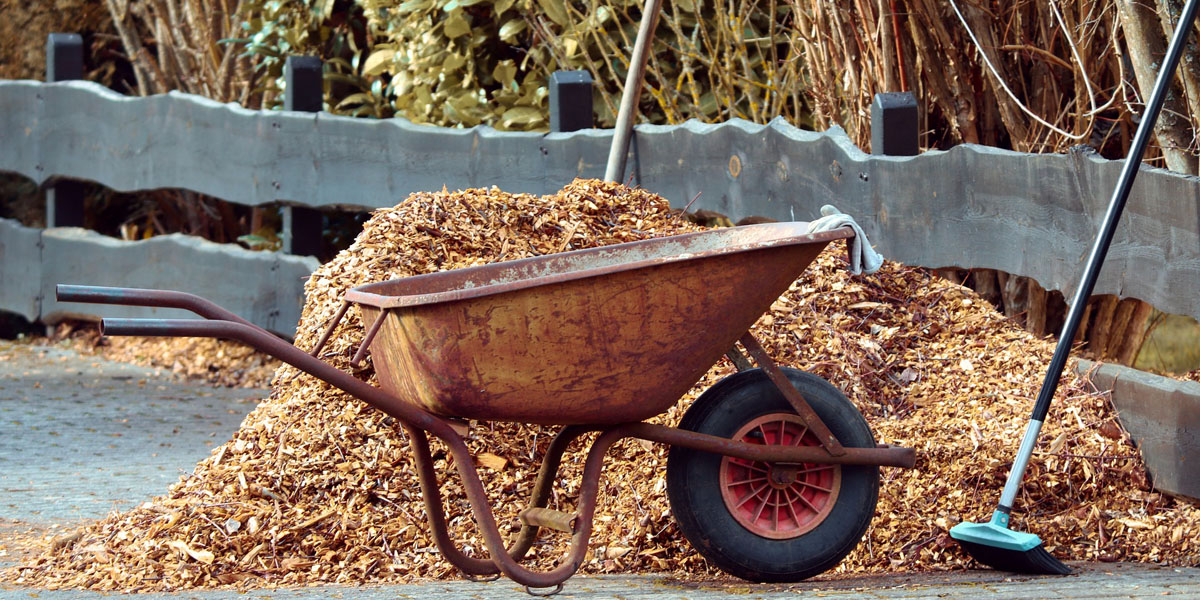 Wood mulch piled up on a driveway with a wheelbarrow in the foreground