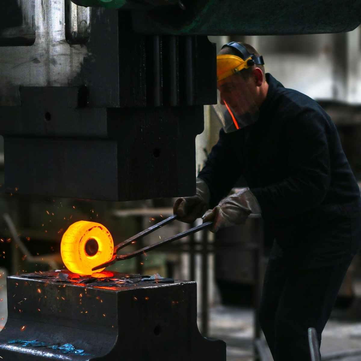 man lifting hot metal