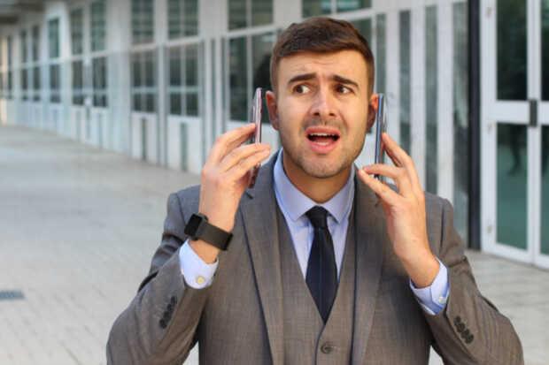 Hombre hablando por dos smartphones