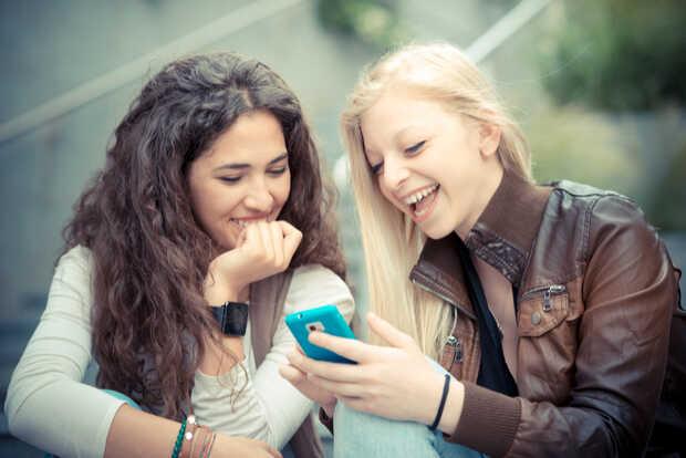 Mujeres con smartphone Facebook introduce encuestas para mostrar publicaciones relevantes