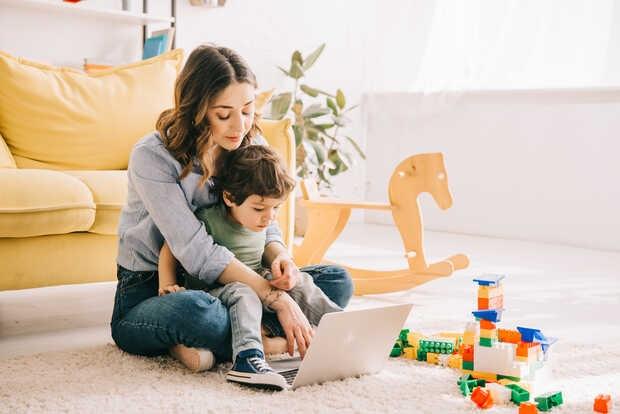 Mamá con hijo y computadora en sala de su casa