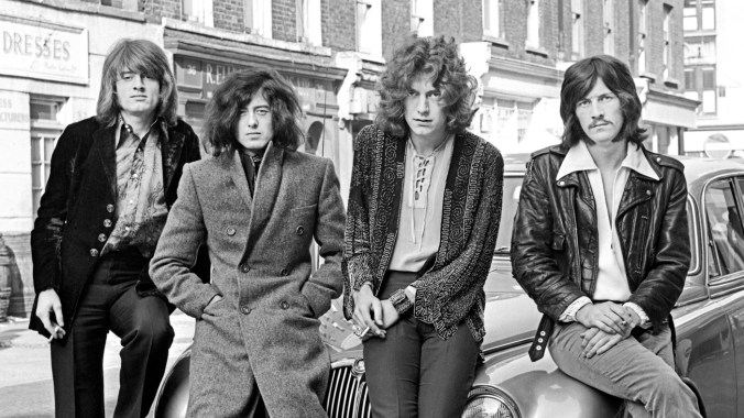 LED ZEPPELIN; L-R: John Paul Jones, Jimmy Page, Robert Plant, John Bonham - posed, group shot, sitting on car bonnet - first photo session with WEA Records in London in December 1968. (Photo by Dick Barnatt/Redferns)