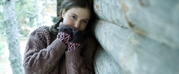 Teen girl leaning against wooden cabin, pulling turtle neck over mouth