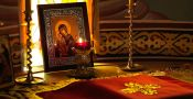 a candle burning in front of an icon of holy mother and child