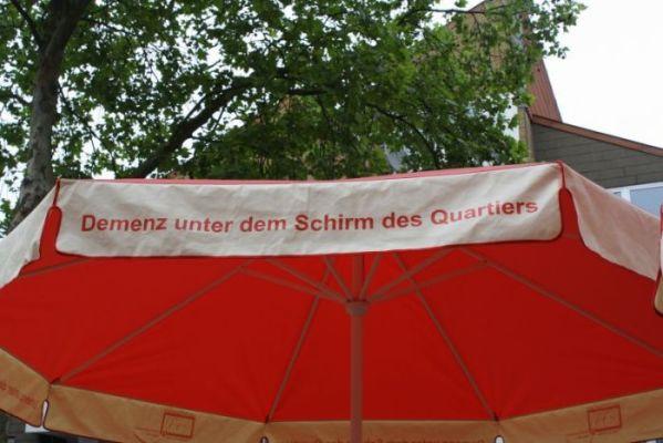 """Foto des roten Schirms mit der Aufschrift """"Demenz unter dem Schirm des Quartiers"""""""