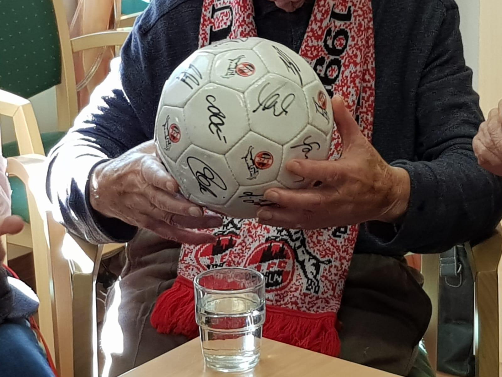 Zwei Hände halten einen signierten Fußball