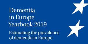 """Titelbild des Beitrags. Zu sehen ist das Titelbild der Jahrbuchs """"Dementia in Europe 2019"""" von Alzheimer-Europe. Ein blauer Hintergrund, auf dem in weiß die Sterne der EU-Flagge abgebildet sind."""