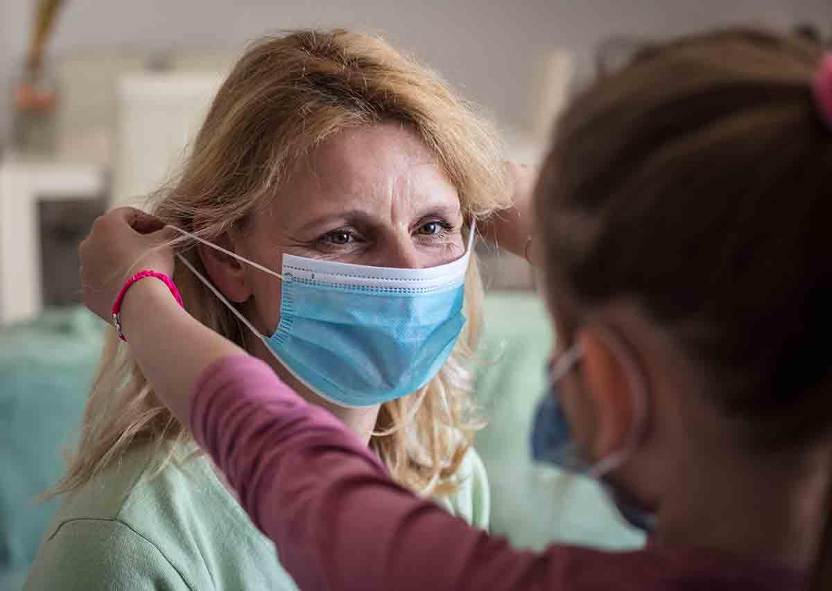 Eine Frau unterstütz eine Angehörige beim Anziehen eines Mundschutzes.