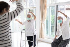 Zwei Seniorinnen betätigen sich sportlich. Sie halten die Abstands- und Hygieneregeln zur Corona-Zeit ein.