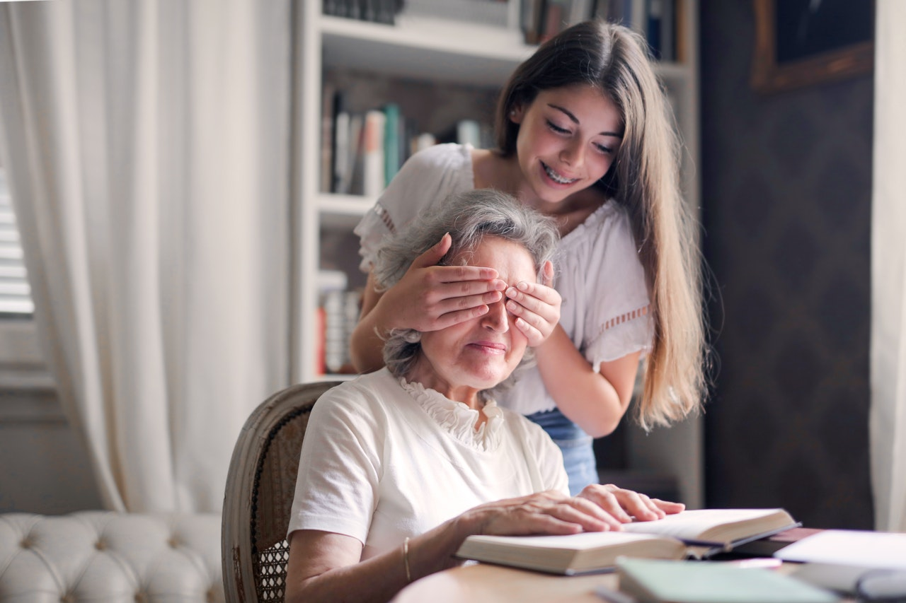 Eine Enkelin verdeckt die Augen ihrer Großmutter und lacht.