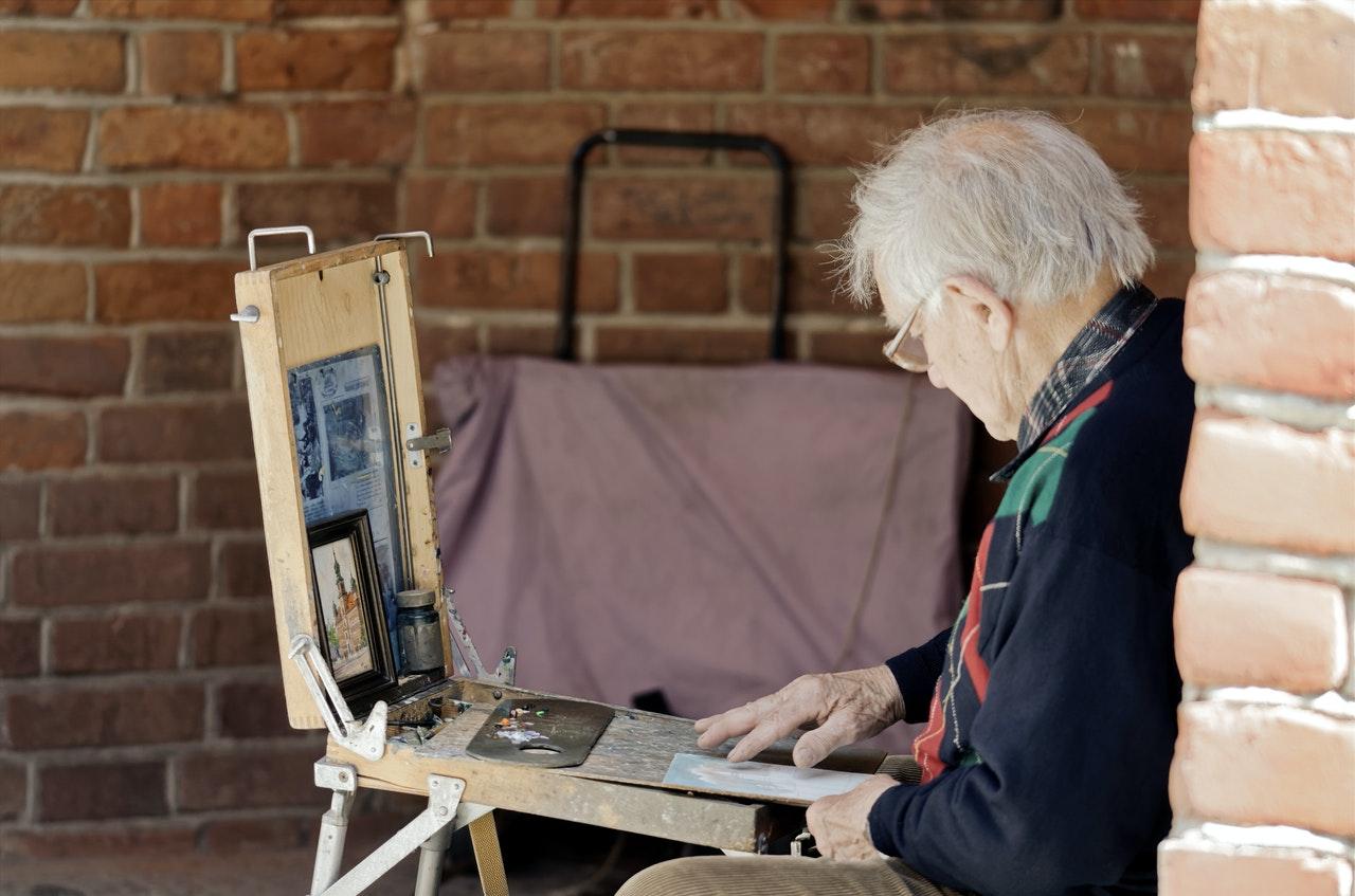 Ein Mann sitzt draußen an einem kleinen Tisch und malt ein Bild.