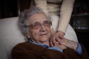 Eine Seniorin sitzt auf einem Sessel und hält die Hand einer jüngeren Frau.