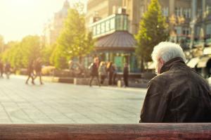 Ein Senior sitzt auf einem Back und betrachtet einen öffentlichen Platz.