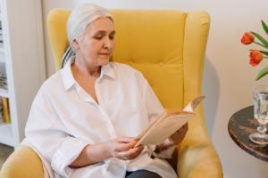 Eine Seniorin sitzt in einem Sessel uns liest in einer Zeitschrift.