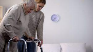 Eine junge Frau hilft einer Senioren am Rollator zu gehen.