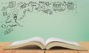 Ein offenes Buch liegt auf einem Tisch. In der linken, oberen Ecke sind Zeichnungen für Ideen und Produktivität. Zum Beispiel eine Glühbirne.