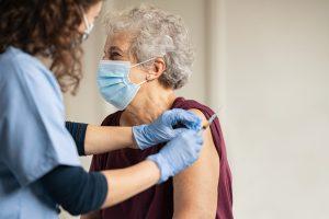 Eine Seniorin erhät eine Schutzimpfung. Alle tragen eine medizinische Maske.