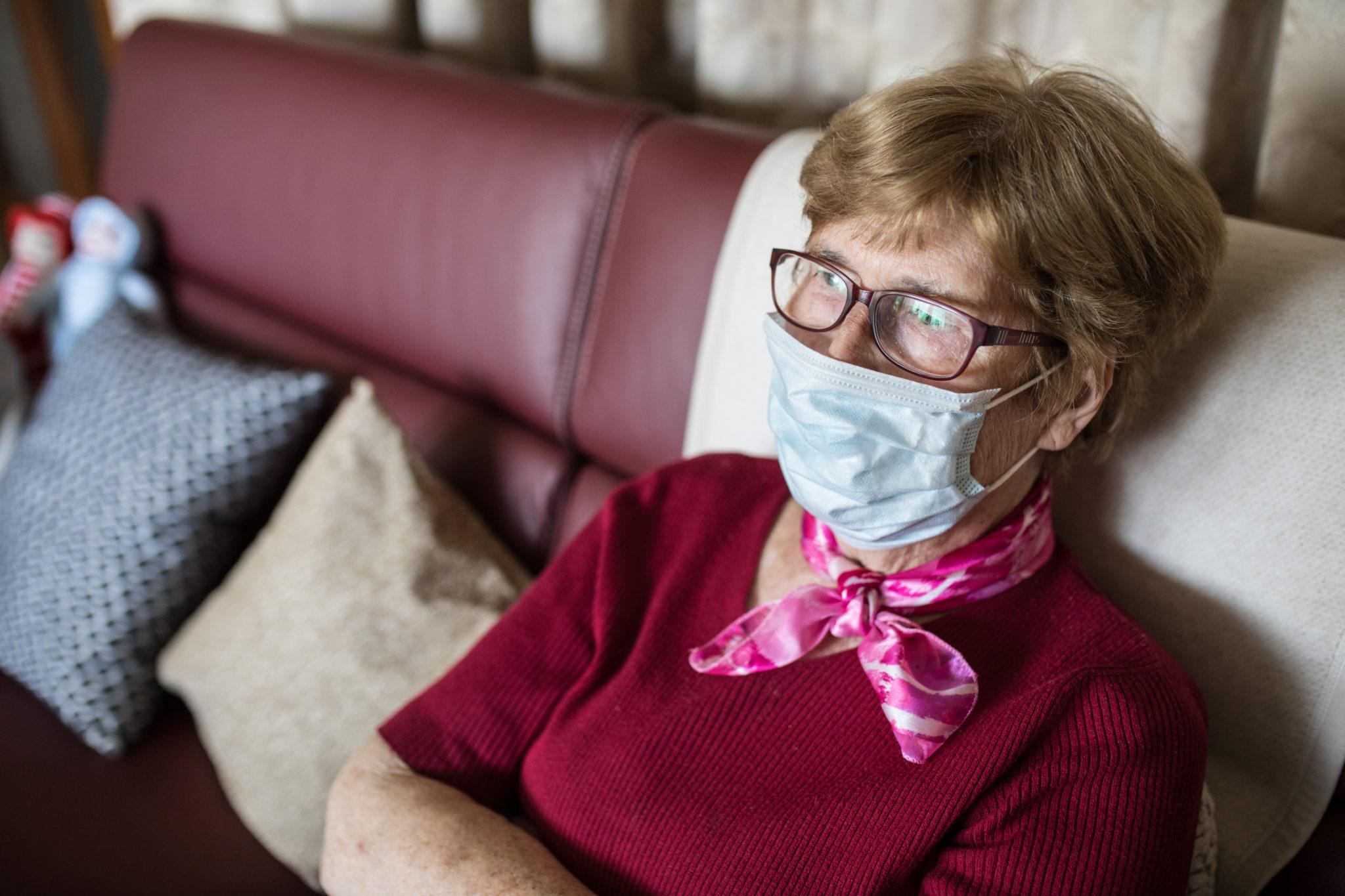 Eine Seniorin sitzt mit Maske auf ihrem Sofa.