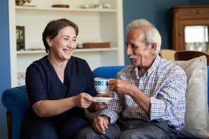 Eine Frau reicht ihrem pflegebedürftigen Vater eine Tasse Kaffee.