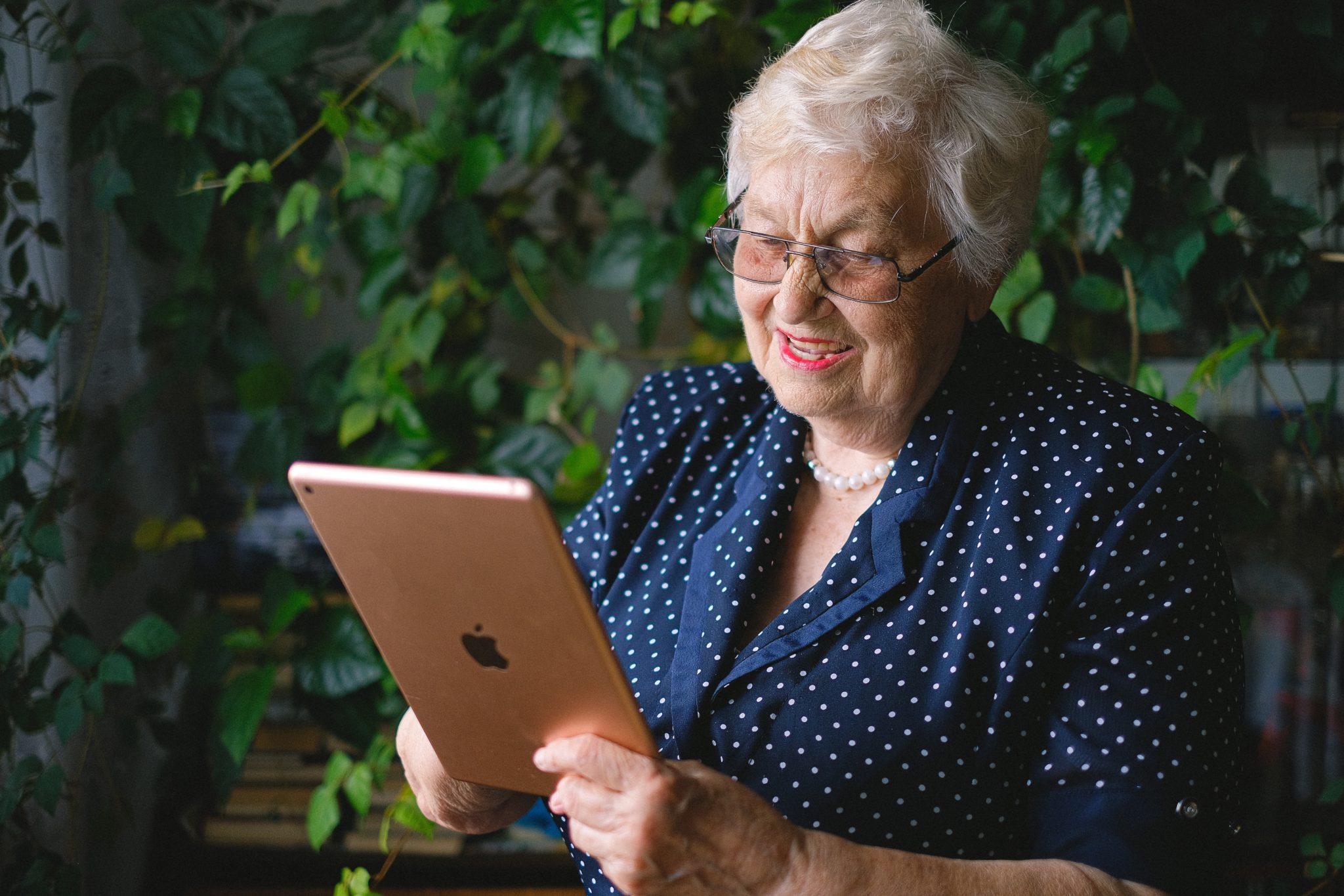 Ältere Dame hält ein iPad und lächelt