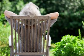 Eine Seniorin lehtn sich bequem auf einem Stuhl zurück und blick in den Garten.