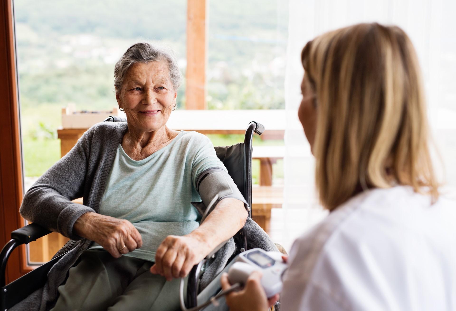 Einer Seniorin in einem sitzen in einem Rollstuhl in lächelt ihr Gegenüber an.