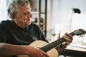 Ein Senior spielt Gitarre.