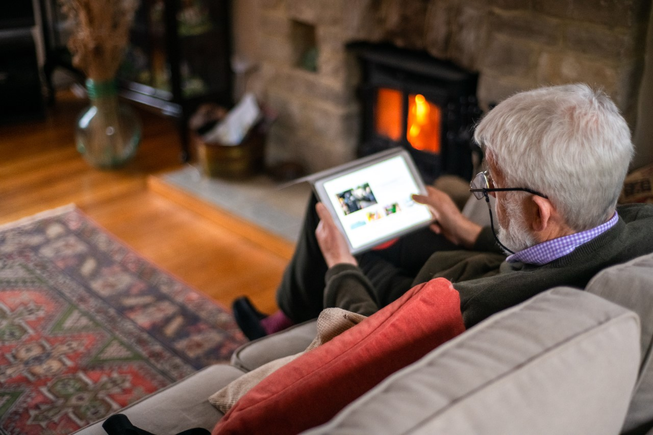 Ein Senior sitzt im Wohnzimmier auf der Couch und bedient ein Tablet.