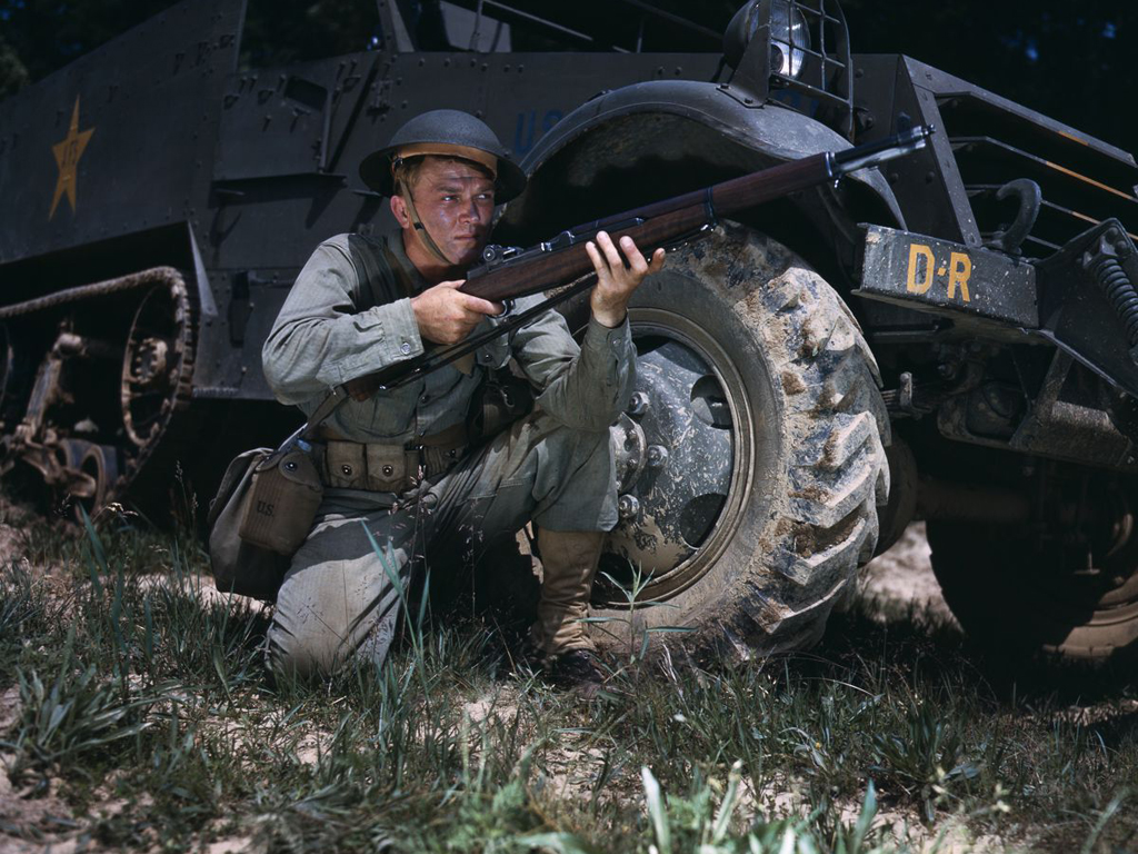 Life at Fort Knox in 1942 - 4. An infantryman uses a half-track for cover while holding an M1 Garand rifle.