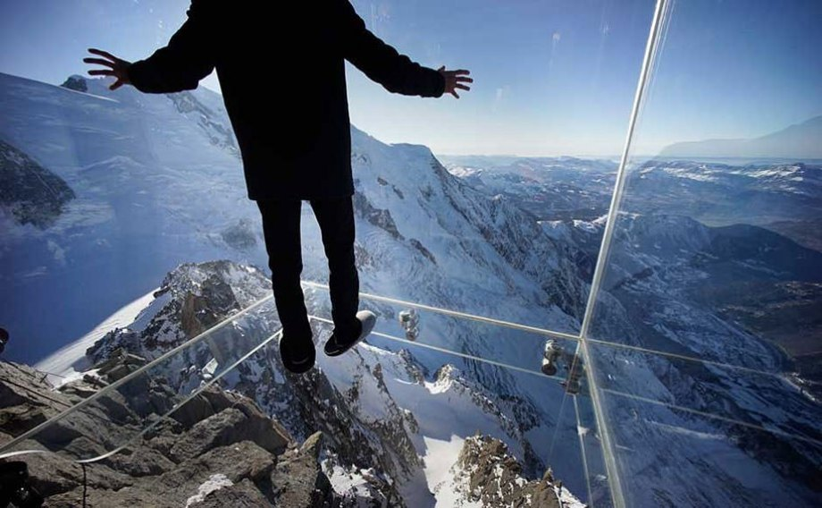 """Atop the 12,600 foot Aiguille du Midi peak is a glass cage named """"Step into the Void."""" Visitors enjoy the view of Mont Blanc, Europe's highest mountain, from what is the world's highest glass floor."""