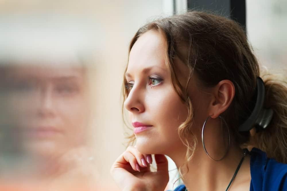 kvinne ser ut av vindu