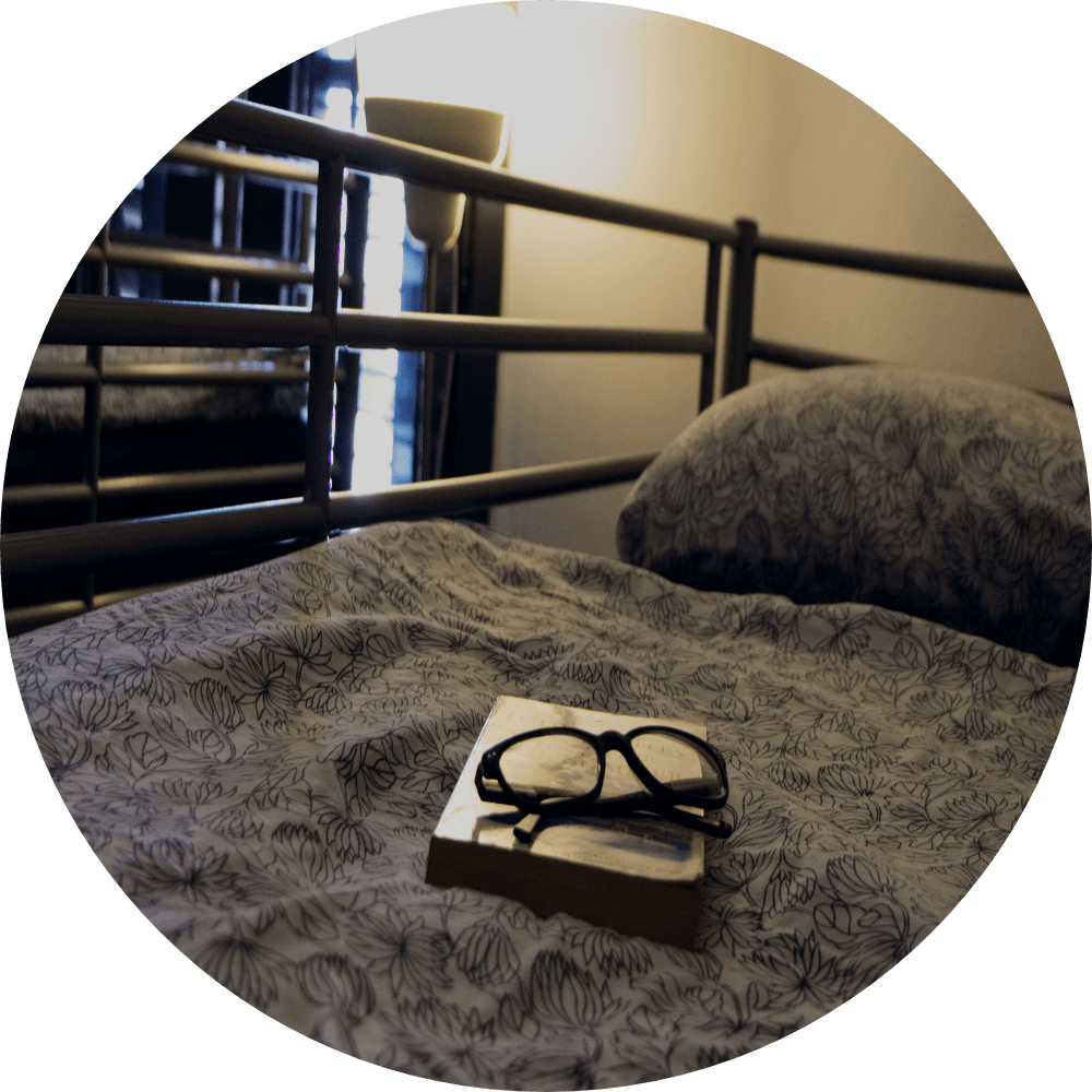 book and glasses on bed