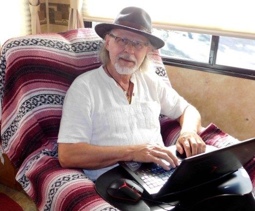 Devon Layne at his 'desk' in his caravan on Alternative-Read.com