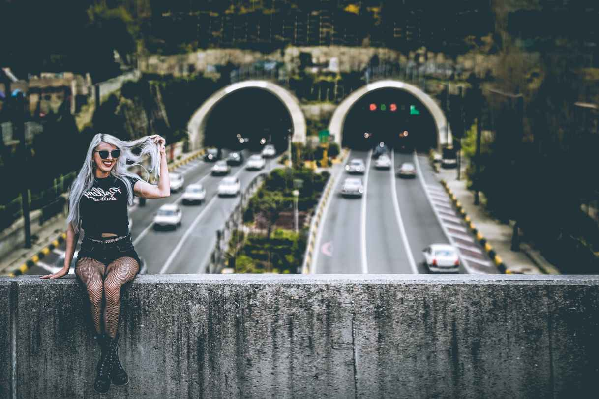 woman wearing black shirt sitting across highways