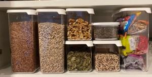 Ei rekke plastboksar med kvitt lok, fylt med frø, nøtter og tørka frukt