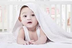 タオルケットをかぶる赤ん坊